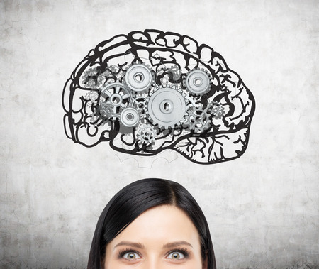 mental work: Image of brain with gears on concrete wall over womans head. Only eyes seen. Concept of mental work.