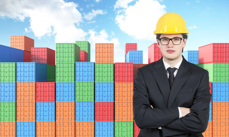 differnt: Businessman in yellow helmet with hands crossed, many sea containers of differnt colours behind. Blue sky above. Front view. Concept of shipping.