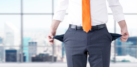 A businessman with an orange tie turning his empty pockets inside out. Front view, no head. Blurred office at the background. Concept of bankruptcy.