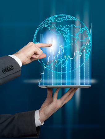 INTERNATIONAL BUSINESS: Mano que sostiene la tableta, la mano de tocar la imagen del holograma de la Tierra sobre ella. Concepto de negocios internacionales.