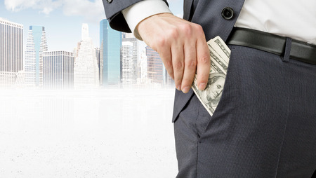 Businessman putting one hundred dollar banknotes into the pocket. Only trousers seen. New York at background. Concept of winning a fortune.