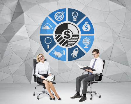 sphere of influence: A smiling woman and a man sitting on castor chairs with books, a circle of business icons between them. Grey geometric background. Concept of cooperation Stock Photo