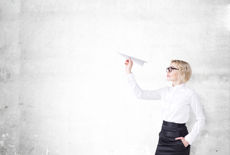 self assured: A woman with a paper plane ready to let it go. Side view. Concrete background. Concept of starting a new project. Stock Photo