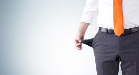 pension cuts: A businessman with an orange tie turning his empty pockets inside out. Front view, no head. Grey background. Concept of bankruptcy. Stock Photo
