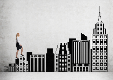 Businesswoman climbing black stairs in shape of New York buildings up to Empire State Building. Concrete background. Concept of career growth.