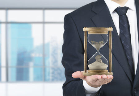 Businessman holding sand glass on palm. Sand running, dollar sign down. Blurred office at background. Concept of time. Stockfoto