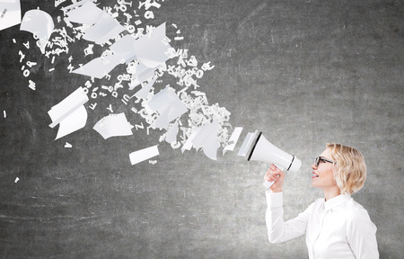 informing: Businesswoman holding white loudspeaker, many letters and paper flying from it. Black background. Concept of informing.