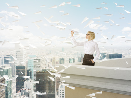 trajectory: Businesswoman with paper plane on roof, Paris and blue sky at background. Concept of new start.