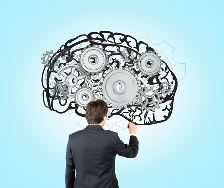 person thinking: Businessman drawing image of brain with gears on blue wall. Back view. Concept of mental work.