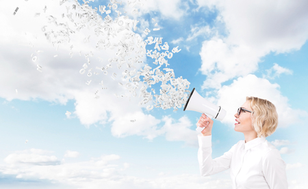 informing: Beautiful woman with white loudspeaker, letters flying from it. Side view. Sky at background. Concept of informing.