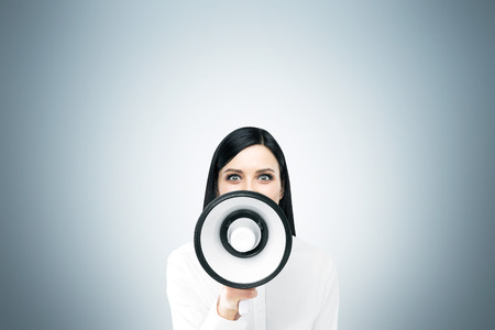 informing: Beautiful woman with white loudspeaker. Front view. Grey background. Concept of informing. Stock Photo