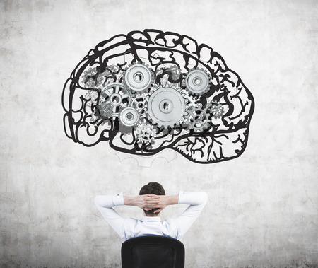 mental work: Businessman sitting on chair with hands on head and looking at image of brain with gears on concrete wall. Back view. Concept of mental work.