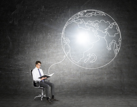 global thinking: Man sitting on chair and reading book. Link to image of Earth from it. Black background. Concept of global thinking.