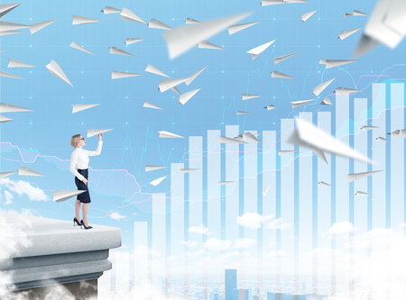 self assured: Businesswoman standing on roof throwing paper plane, city view, planes flying around. Blue sky and bar charts at background. Concept of starting new project.