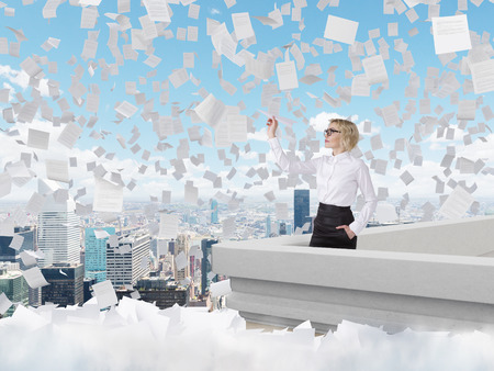 self assured: Businesswoman standing on roof throwing paper plane, Paris view, papers flying around. Blue sky at background. Concept of starting new project.
