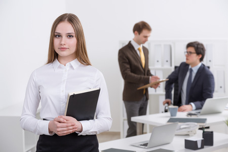 datebook: Young businesswoman with datebook, two colleagues at background. Concept of team work. Stock Photo