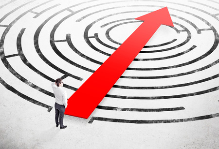 alumni: Businessman with hand on head standing on white floor in front of painted labyrinth, thick red arrow through it. Concept of finding solution.