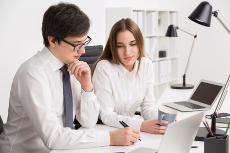 Young businessman looking at laptop screen and making notes, businesswoman next to him looking at notes. Concept of explanation.