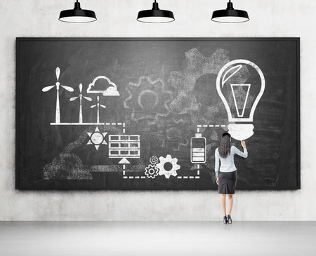 alternative energy sources: Businesswoman drawing symbols of alternative energy sources on black chalk board. Concrete background. Concept of clean environment. Stock Photo