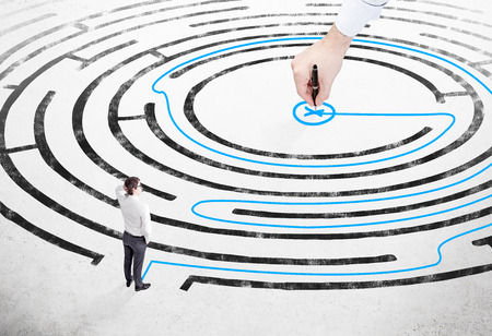 hesitation: Businessman with hand on head standing on white floor in front of painted labyrinth, hand drawing blue way out. Concept of finding solution.