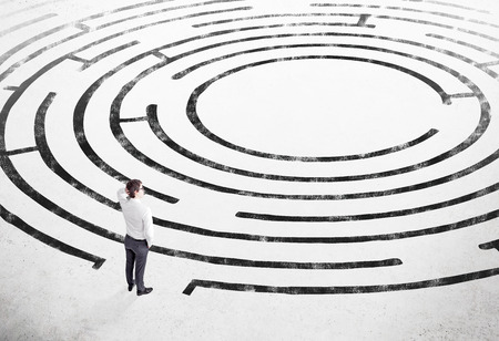 alumni: Businessman with hand on head standing on white floor in front of painted labyrinth. Concept of finding solution.