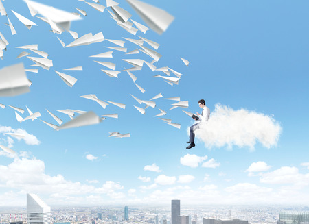 stack of papers: Man sitting on pile of books reading, paper planes flying from book. Blue sky and city at  background. Paris. Concept of reading. Stock Photo