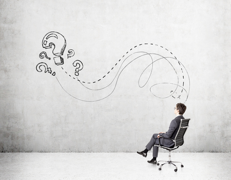 hesitation: Businessman sitting on chair. Concrete wall with question marks in front. Concept of solving problem. Stock Photo