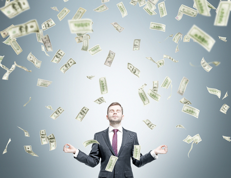 win money: Businessman in posture of meditation, dollars falling from above. Grey background. Concept of getting money. Stock Photo