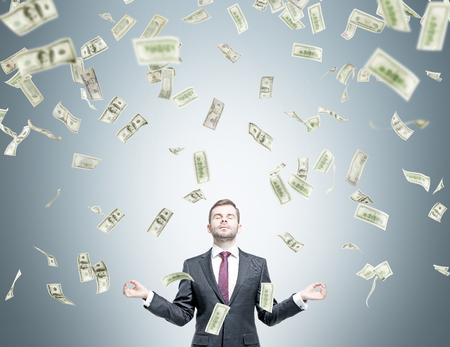hombre cayendo: Hombre de negocios en postura de meditación, los dólares que caen desde arriba. Fondo gris. Concepto de conseguir dinero.