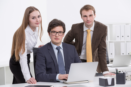 front office: Three businesspeople at one laptop, looking in front, office background. Concept of team work.
