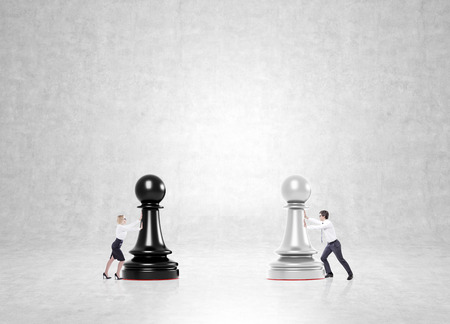 business game: Businessman and businesswoman pushing black and white pawns to each other. Concrete background. Concept of business game. Stock Photo