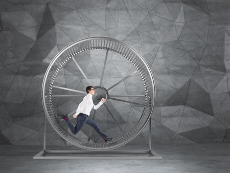 routine: Businessman running in spinning wheel. Grey geometric background. Concept of hard work.