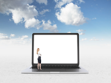 prospects: Businesswoman standing in front of huge blank laptop screen. Side view. Blue sky at background. Concept of expectations. Stock Photo