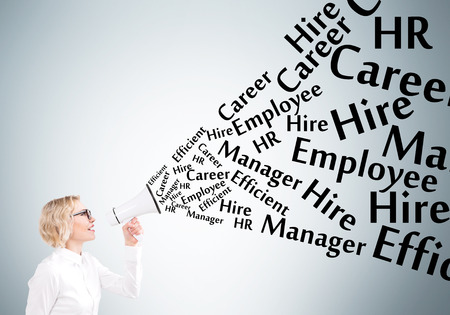 informing: Businesswoman holding white loudspeaker, many employment words from it. Grey background. Concept of informing. Stock Photo