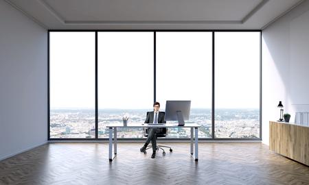 Hombre de negocios sentado a la mesa en la oficina grande. ventanal detrás. Vista de la ciudad. Concepto de trabajo. Foto de archivo - 54165547
