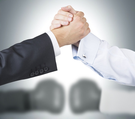double game: Two raised shaking hands, two blurred hands in boxer gloves at background. Concept of double game. Stock Photo