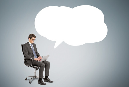 remark: Businessman with laptop sitting on chair, remark cloud to the right. Grey background. Concept of searching information.