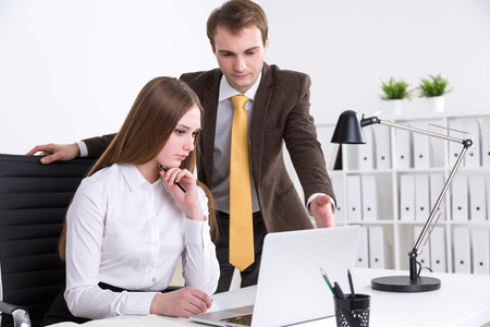Businessman standing at businesswoman and pointing at computer screen, office at background. Criticism. Concept of cooperation.