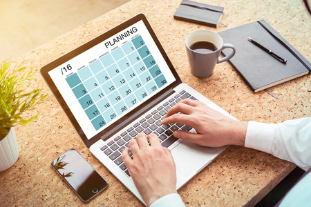 file clerks: Hands typing on laptop, calendar on screen. Cork table, stationary around. Concept of planning.