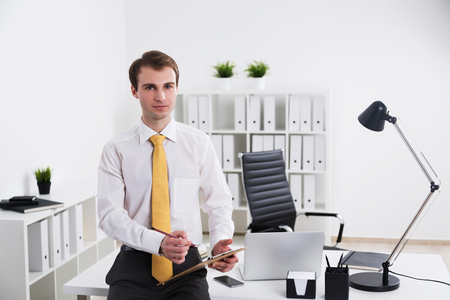 front office: Businessman making notes on notepad and looking in front, office. Concept of work.