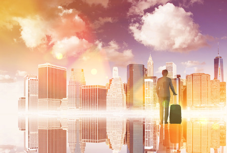 graduation suit: Businessman with suitcase standing in front of New York view and its reflection. Back view. Concept of dream.