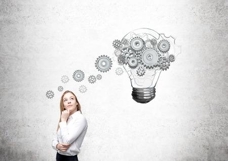 Femme d'affaires en levant, ampoule avec engrenages peint ci-dessus. Vue de face. Fond de béton. Concept de nouvelle idée. Banque d'images