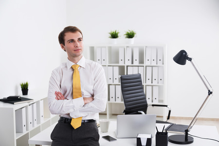 mani incrociate: Imprenditore in piedi con le mani incrociate e guardando a parte, ufficio al fondo. Concetto di lavoro.