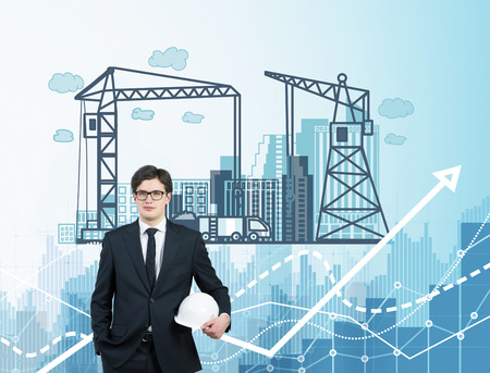 difficult task: Businessman with white helmet, picture of construction process behind. Blue background with graphs and charts. Concept of city construction. Stock Photo