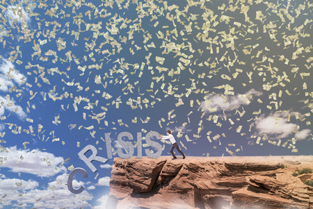 coping: Businessman pushing letters of word crisis from rock. Blue sky and dollars fall at background. Concept of coping with crisis. Stock Photo