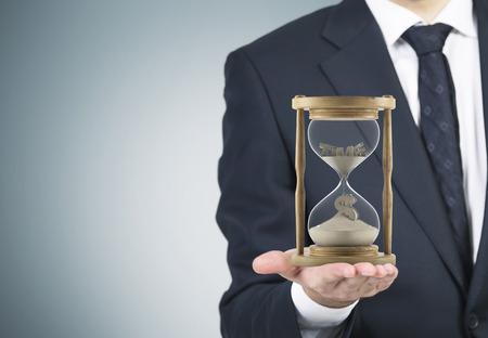 El hombre de negocios la celebración de reloj de arena en la palma. Correr en la arena, signo de dólar hacia abajo. Fondo gris. Concepto del tiempo. Foto de archivo