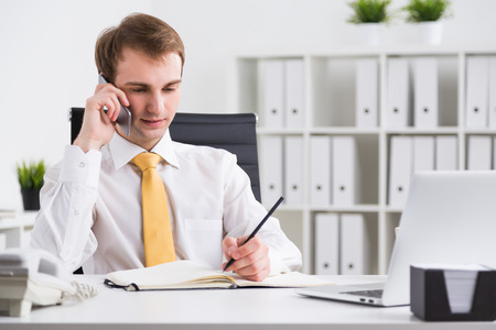 file clerks: Businessman speaking on phone and making notes, office at background. Concept of communication.