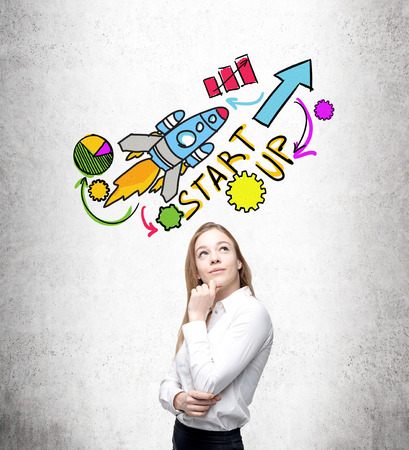 Businesswoman with hand on chin thinking, startup pictures over her head. Concrete background. Concept of start up. Stock Photo