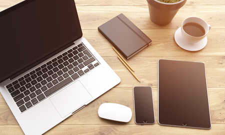 datebook: Laptop, smartphone and tablet with black screens, coffee, plant, pencils and datebook on wooden table. Concept of workplace. Mock up. 3D rendering