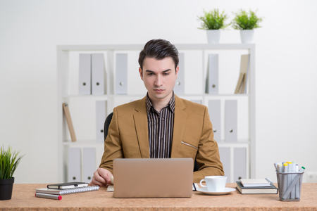 internet search: Businessman in smart suit at table, working on computer. Office at background. Concept of work.